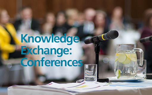 Photo of microphones on a table in a crowded room wit the words Knowledge Exchange: Conferences